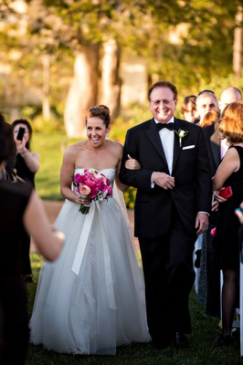 Bride in Monique Lhuillier dress walks down aisle with father of the bride