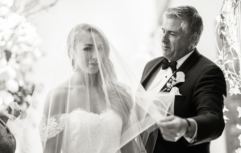 Black and white photo of father of bride removing veil at wedding ceremony touching moment