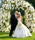 Bride in a strapless Pnina Tornai gown with groom in a black tuxedo and white bow tie at floral arch
