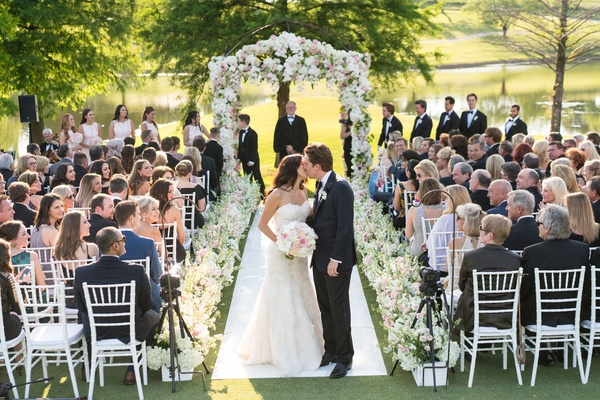 Bride and groom stop and share kiss after walking up aisle guests watching pink and white flowers