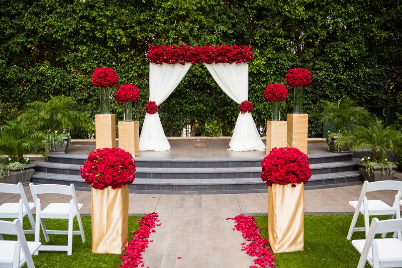 Red Roses On Gold Wrapped Bases White Drapery Aisle