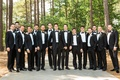 Groom and groomsmen in tuxedo suits with bow ties in wooded area georgia wedding
