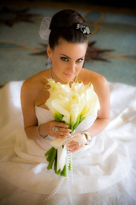 Bride in high bun with netted veil and calla lily bouquet