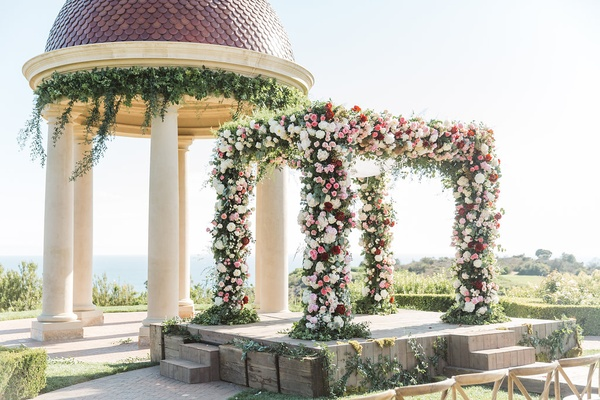 floral vibrant chuppah front of dome pelican hill resort newport wedding red pink arch california