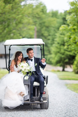 wedding ceremony exit bride in trumpet gown and groom in tuxedo on back of golf cart new york