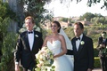 bride in vera wang ball gown walked down the aisle by her two dads
