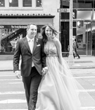 black and white photo of couple running streets of new york city wedding dress suit crosswalk
