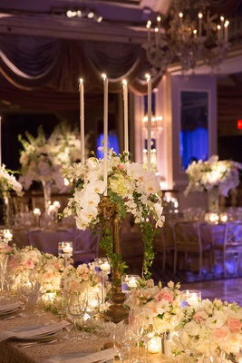 a tall candelabrum featuring cascading green foliage and white orchid flowers on long table