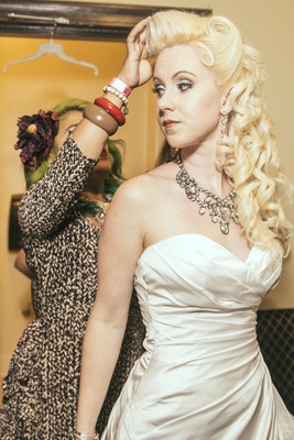 Bride getting hair done wearing costume diamond necklace