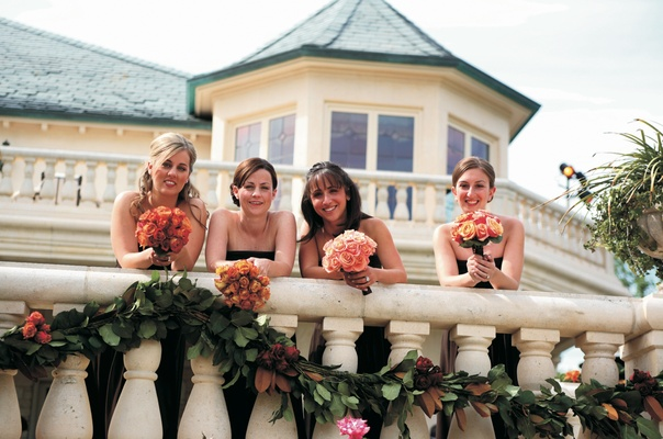 Bridesmaids carry orange and pink bouquets