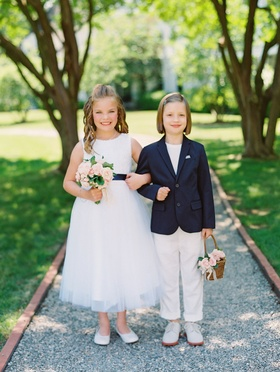 Wedding ceremony two flower girls one in dress and one in blazer and slacks basket pink flowers