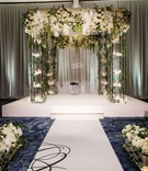 wedding ceremony ballroom aisle runner white stage chuppah candles white flowers greenery on stage