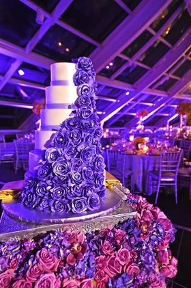 White wedding cake with lavender bands, dark purple sugar roses, crystals surrounded by violets