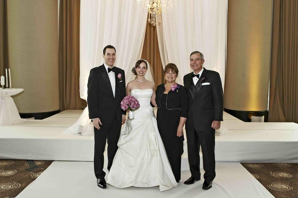 Bride and groom in ceremony ballroom with mom and dad