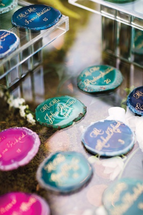 pink, teal, and blue agate slices used as escort cards with gold calligraphy