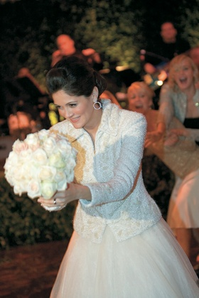 Bride tosses white bouquet to friends and bridesmaids