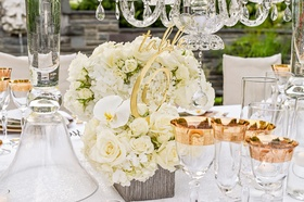 gold laser cut table number placed in small, white floral arrangement of roses, hydrangeas, orchids