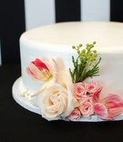 White wedding shower cake with pink and white roses and tulips, greenery