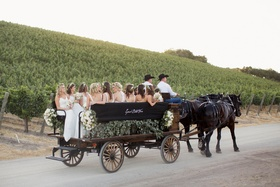 Bridesmaids sitting in trough of old carriage