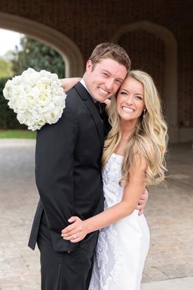 bride in romona keveza wedding dress with brocade applique, groom in black suit