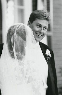 groom smiles at bride wearing wedding veil