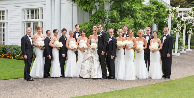 Bride and groom with tuxedo groomsmen and white dresses