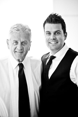 Black and white photo of groom with father in groom's suite