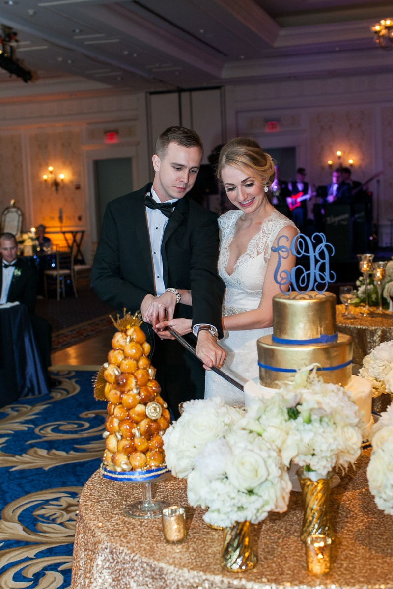 USMC groom in tux cuts wedding cake with sword