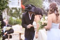 father of the bride in black cowboy hat, bride in monique lhuillier crop top wedding dress