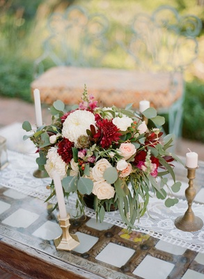 Wedding rehearsal dinner welcome party gold candleholders and vase filled with greenery rose dahlia