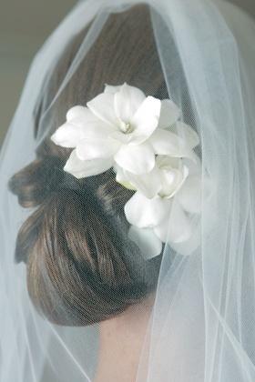 Bride's low bun with two gardenias and veil
