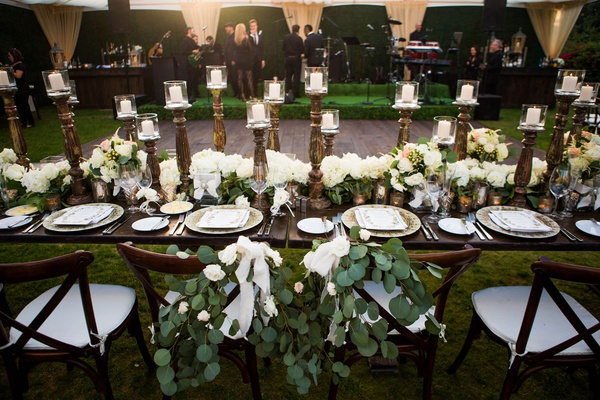 wedding reception wood dance floor wood table vineyard chairs greenery white flowers antique candles