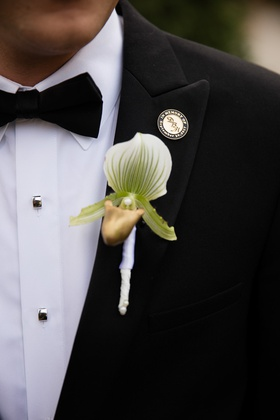 single, large white, green, and gold orchid as boutonniere
