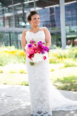 a bride in fitted lace gown with bright bold bouquet pink purple white flowers