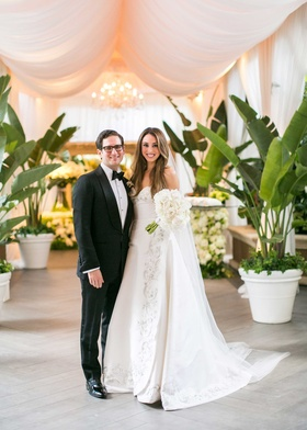 Bride in Oscar de la Renta wedding dress with white peony bouquet groom in tuxedo bow tie by drapery