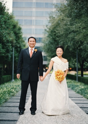 Bride in a strapless dress with a Burberry wrap and groom in a black tuxedo and orange tie