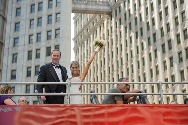 Bride and groom take a photo aboard a sight-seeing bus