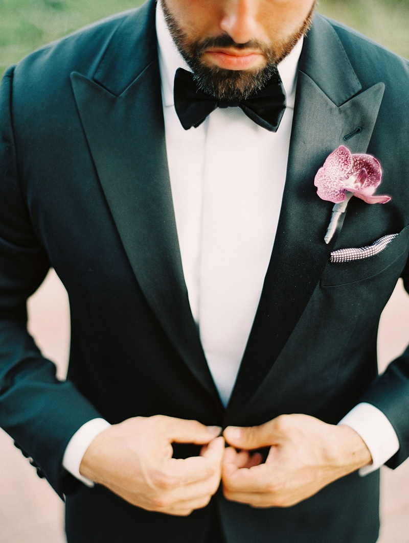 groom in black tuxedo and white shirt with purple orchid boutonniere gets ready for wedding