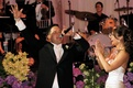 Bride claps next to groom with microphone at wedding reception