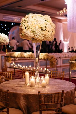 Round wedding reception table with tall ivory flower arrangement and candle grouping at base