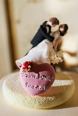 Cake topper of groom figurine dipping bride figurine and heart with bride and groom's names