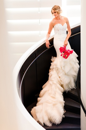 bride in strapless lazaro corset dress with long ruffled train