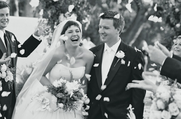 Black and white photo of couple walking up aisle with petals