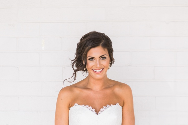 bride smiling with hair back and strapless sweetheart dress