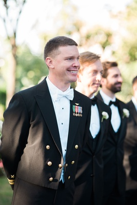 Groom in white bow tie and Navy military uniform seeing bride for first time in wedding dress
