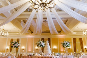 wedding reception grand chandelier with drapery cake under light fixture classic ballroom reception