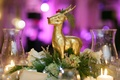 Holiday wedding reception table with a gilded reindeer, evergreen, green hydrangeas, white roses