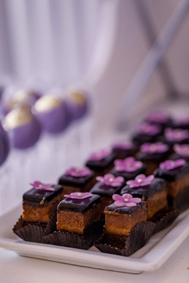 Chocolate ganache bite size wedding reception dessert with edible purple flower decoration pearl dot