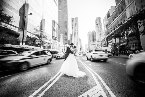 black and white photo of bride and groom kissing in the missing of the street in chicago