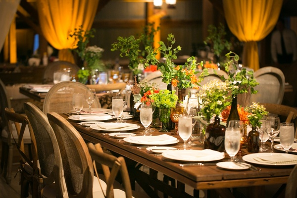 Wood table with no runner at wedding reception and greenery